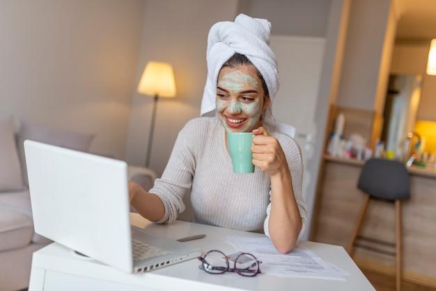 女の子は自宅で働いており、フェイスマスクを着用しており、バスローブを着ています。