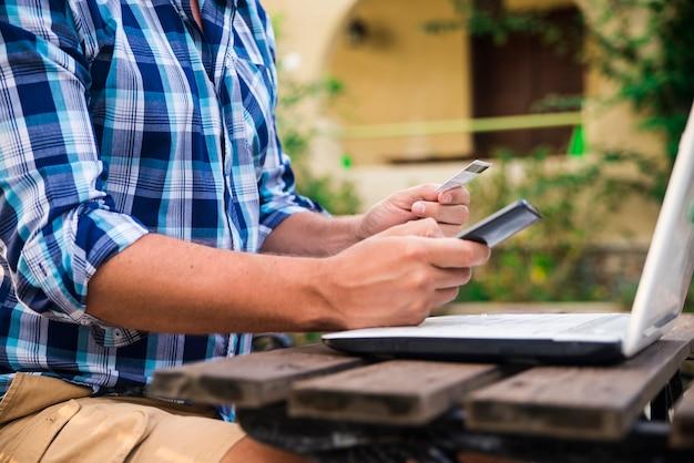Красивый человек, расслабляющий в своем саду, используя ноутбук, чтобы делать покупки в солнечный день