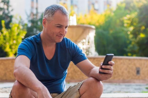 Закройте вверх портрет счастливой улыбкой сорок лет кавказских человек, разговариваете по мобильному телефону на открытом воздухе