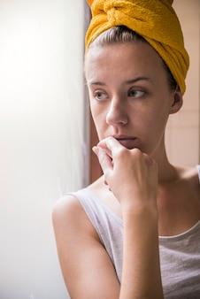 憂鬱な女性。シリーズ。窓から見える悲しい少女、ヴィンテージフィルター。