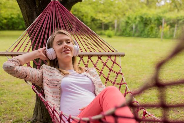 携帯電話で音楽を聞くハンモックに横たわっている女性の肖像画を閉じます。陽気な少女は、屋外の赤いハンモックで楽しむ。女性、イヤホンで音楽を聴く外でリラックス