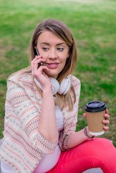 若い女性はコーヒーを携帯電話とヘッドフォンを使って手に入る。若いスタイリッシュな美しい女の子、音楽、携帯電話、ヘッドフォン、楽しんで、笑顔、幸せ、クールなアクセサリー、ヴィンテージスタイル、楽しみ、笑い、公園を聴く