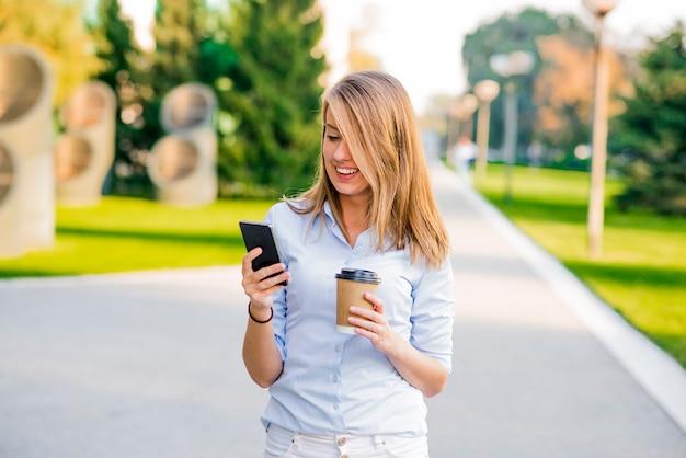 仕事の休憩中に会社の廊下を歩いている間に金融ニュースに関する情報を読んでいる自信のある女性、オフィスに秘書と共に行く間にクライアントがテキストメッセージを書く成功したビジネスマン