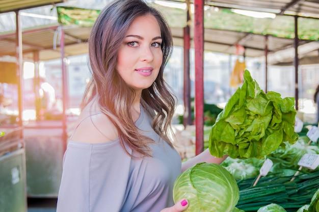 Сырая пища, концепция вегетарианства. портрет улыбается красивая девушка в повседневной одежды, проведение капуста в ее руках. здоровая кожа, глянцевые каштановые волосы.