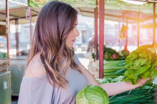 生の食べ物、野菜のコンセプト。彼女の手にキャベツを持っているカジュアルな服の中に笑っている美しい女の子の肖像画。健康な肌、光沢のある茶色の髪。