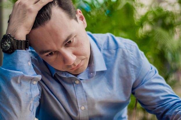 ストレスのある男。感情の肖像画、単独の男。屋内の肖像画。額に手を持つうつ病のビジネスマン