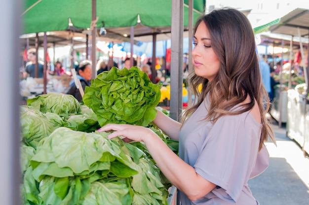緑の市場で緑豊かな野菜を選択している美しい若い女性の肖像画。健康的な食品の買い物の概念。緑の市場で野菜を買っている若い女性。