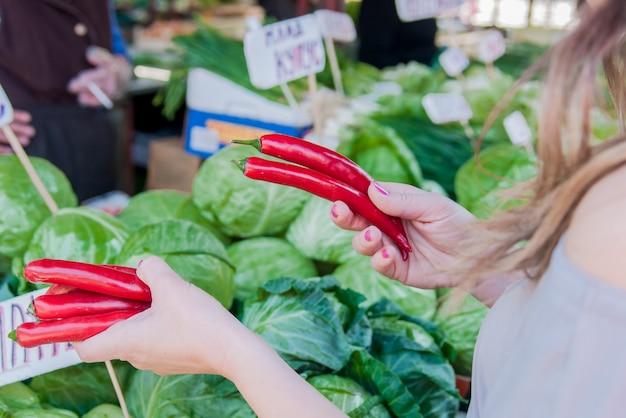 クローズアップの概念。地元の緑の市場で野菜を選ぶ。君
