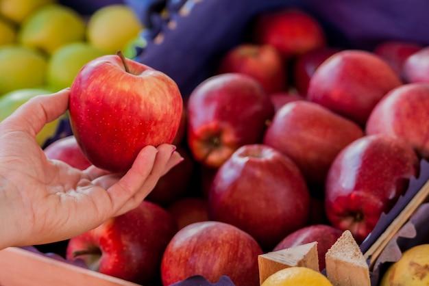 最高の果物と野菜だけ。リンゴを包む美しい若い女性。緑色の市場で新鮮な赤いリンゴを買う女性..スーパーマーケットで有機リンゴを買う女性