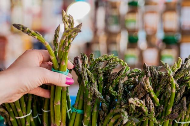 女性はアスパラガスを買う。女性の手で新鮮なアスパラガスの束。女の子、クローズアップ、アスパラガス、健康的な食事のコンセプト