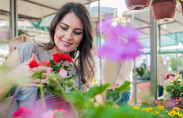 ガーデニングセンターで粘土ポットにゼラニウムを保持している若い女性。マーケットガーデンの中心で花を買い物する若い女性