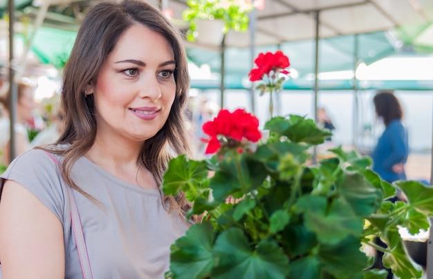 ガーデニングセンターで粘土ポットにゼラニウムを保持している若い女性。ガーデニング、植え付け - ゼラニウムの花を持つ女性