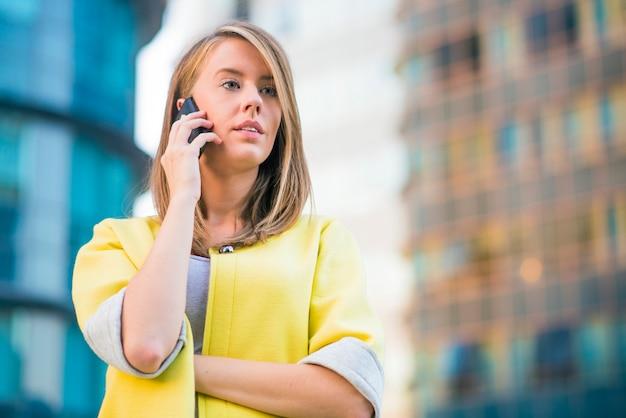 成功した実業家または起業家が彼のオフィスの前に携帯電話の立場で話しています。