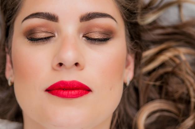 Гламурный портрет красивой модели женщины со свежим ежедневным макияжем и романтической волнистой стрижкой. модный блестящий маркер на коже, сексуальные глянцевые губы и темные брови