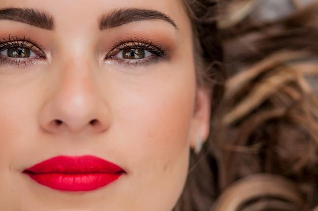 美人女性のポートレート。緑の目を持つブルネットのためのプロフェッショナルメイク - 赤い口紅、スモーキーアイズ。美しいファッションモデルガール。パーフェクトスキン。化粧。白い背景で隔離されています。顔の一部