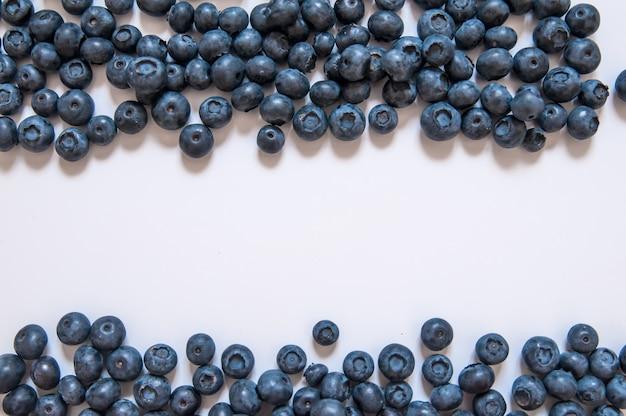 新鮮な甘いブルーベリーフルーツとミントの葉のコピースペース。デザート健康食品。熟した青ジューシーなオーガニックベリーのグループ。ウェブサイト用、バナーデザイン。白い背景に隔離されています。