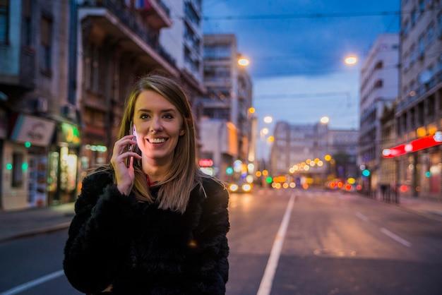 彼女の携帯電話、都市のスカイラインの夜の光の背景を使用して女性。美しい女の子の肖像画。豪華なブルネットの女の子、夜の都市のライトの肖像画。スマートフォンで美しい女の子のメッセージ