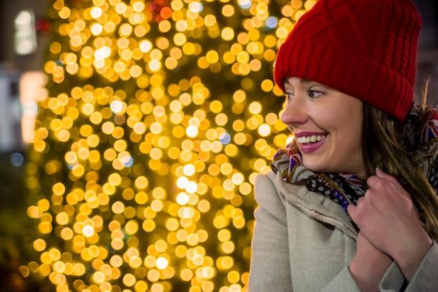 Вид сбоку женщина на праздничном рождественский рынок в ночное время счастливый женщина, глядя вверх с рождественский свет в ночное время