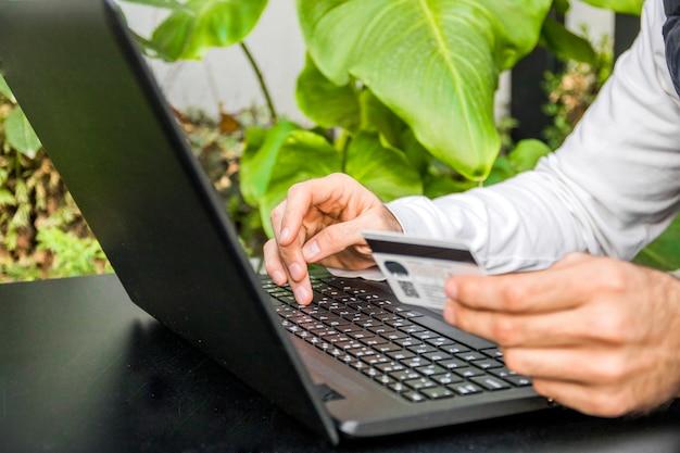 Мужчина покупает онлайн со своей кредитной картой со своего портативного компьютера. крупный план человека покупки онлайн с помощью ноутбука с кредитной карты