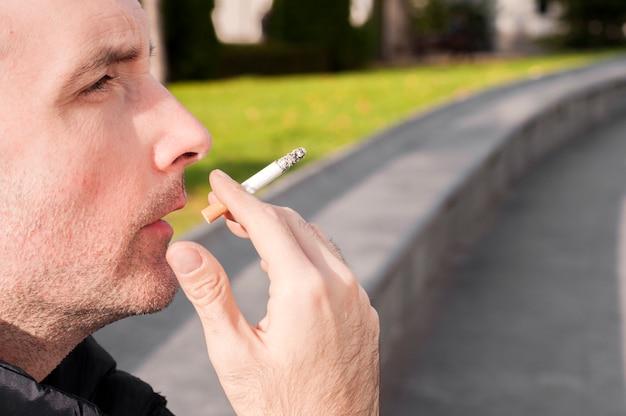 若い、スタイリッシュ、若い、喫煙、都市、セービング、屋外、晴れた日に屋外のタバコを吸うハンサムな白人
