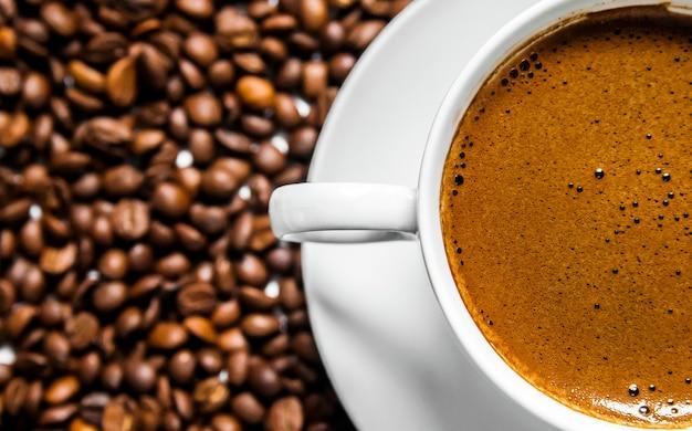 コーヒーカップとテーブル上のコーヒー豆、トップビュー、愛のコーヒー、白い背景に茶色のコーヒー豆、コーヒー豆とホットコーヒーカップ