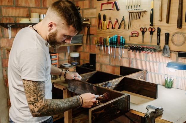 クラフトワークショップで木製の家具にニス塗料を塗る