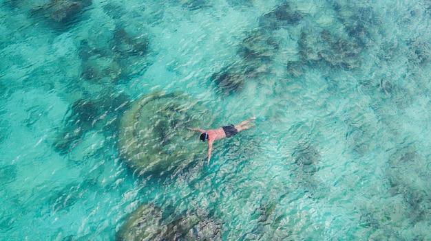 楽園の澄んだ水でシュノーケリングを泳ぐ休暇観光シュノーケル男。結晶水とサンゴ礁で少年シュノーケラーを泳ぎます。ターコイズブルーの海の背景。