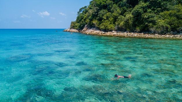 澄んだ青い結晶水とサンゴ礁の上の熱帯の海で一人でシュノーケリングの男。ペルヘンティアン島、マレーシア