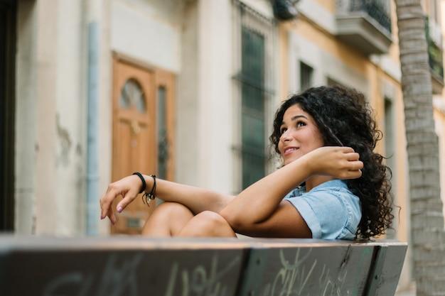 Вдумчивый девушка сидит на скамейке