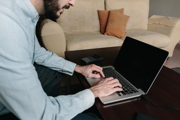 自宅のソファーに座っているラップトップでオンラインで作業する男性。在宅勤務とリモートワークのコンセプト