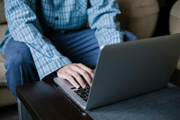 Человек в ночном люксе сидит на диване и работает удаленно из дома
