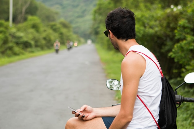 Молодой турист наездник с солнцезащитные очки, ожидание на своем мотоцикле и проверка смартфона