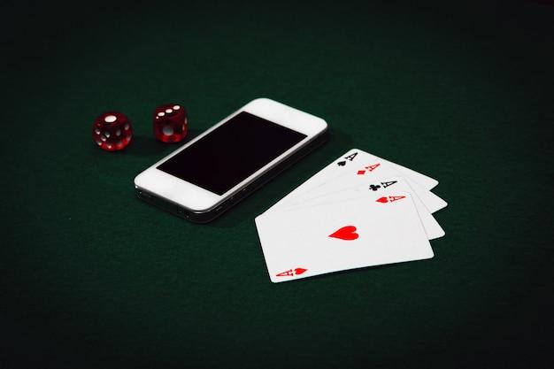 緑のテーブルの上のスマートフォン、サイコロ、カードのクローズアップトップビュー。ポーカーオンラインコンセプト。