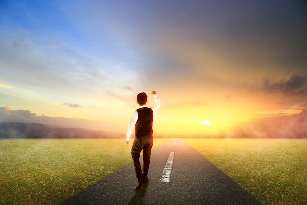 朝の日の出と高速道路の道を歩いてビジネス男