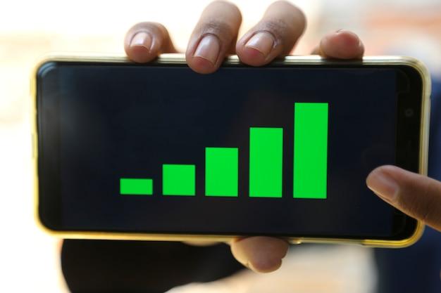 Привлекательные руки, показывая график прибыли на смартфоне