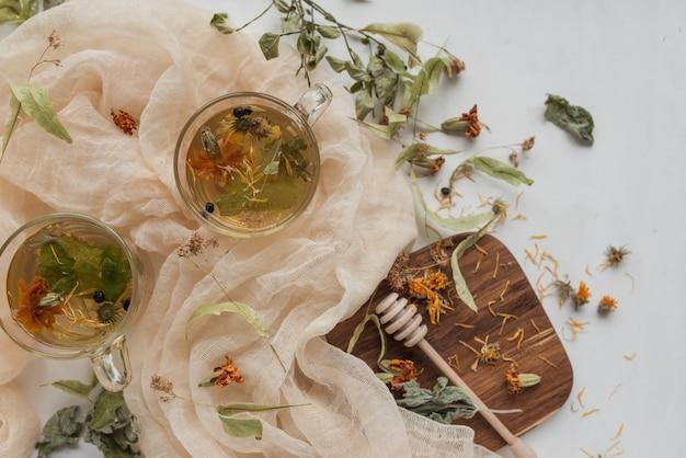Заваривали травяной чай в стеклянных чашках и деревянной доске. ингредиенты травяного чая