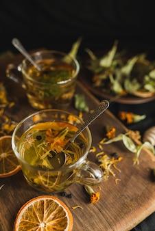 Заваренный травяной чай в стеклянных чашках на деревянной доске. ингредиенты для травяного чая. сушеная мята, черника, цветы липы, цветок календулы, цветки календулы.