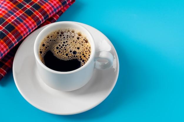白いソーサーにコーヒー、青に赤の市松模様ナプキン