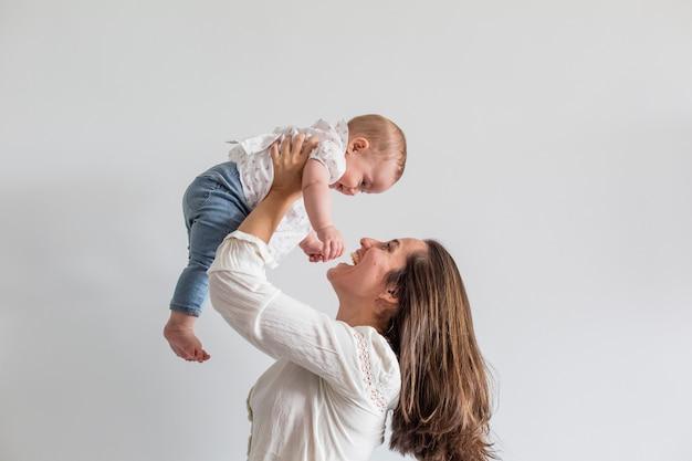 女の赤ちゃんと彼女の母親が家で遊んで