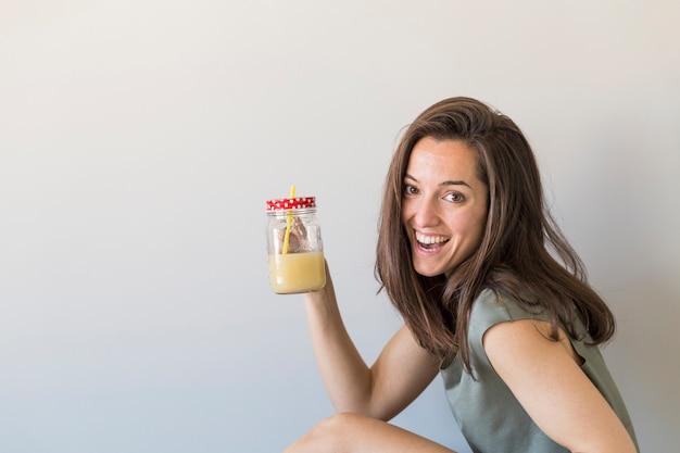 健康なジュースを手に楽しんで、笑顔の美しい若い女性。