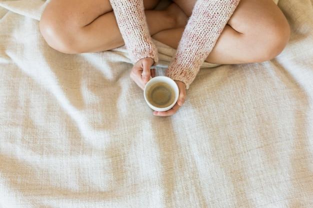 Молодая женщина, наслаждаясь ее кофе, сидя в кровати. вид сверху.