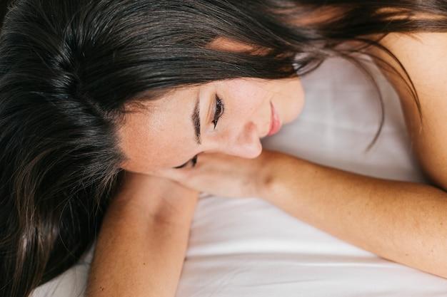 Молодая красивая женщина, отдыхая на кровати. образ жизни дома. в закрытом помещении. портрет