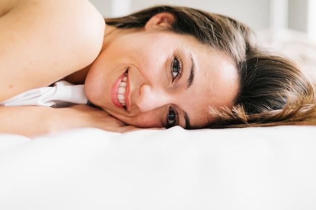 Молодая красивая женщина, сидя на кровати, отдыхая и улыбаясь. образ жизни дома. в закрытом помещении. портрет