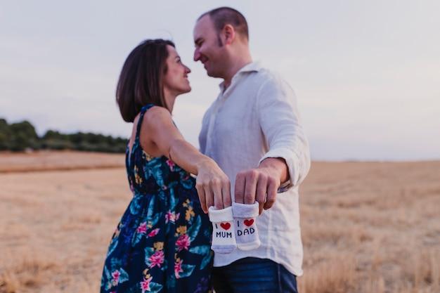 Портрет на открытом воздухе молодой беременной пары в желтом поле. семейный образ жизни на открытом воздухе. держа в руках детские носки, я люблю маму, я люблю папу
