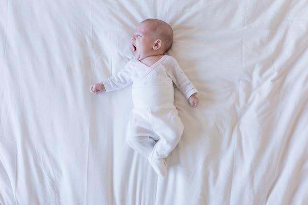 自宅で白い背景にあくび美しい赤ちゃんの肖像画を閉じる