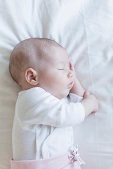 自宅の白い背景の上の美しい赤ちゃんの肖像画を閉じる