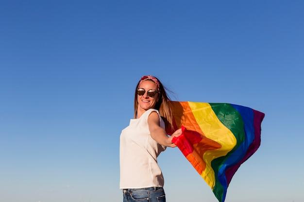 屋外の青い空にゲイレインボーフラグを保持している女性。
