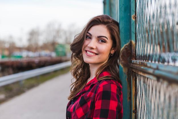 フェンスのそばに立っている若い美しい女性。
