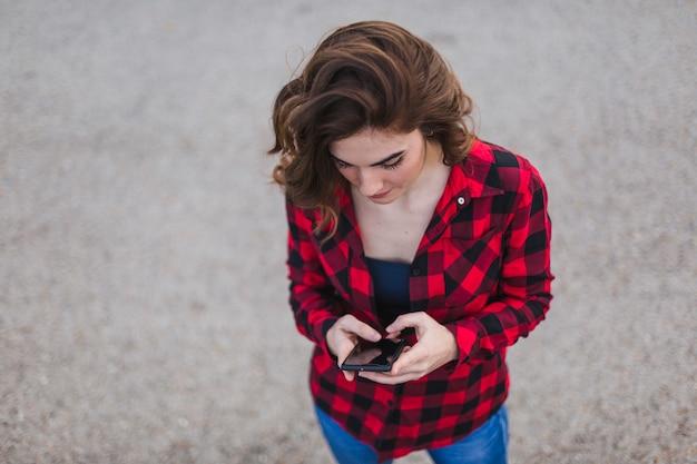 携帯電話を使用して若い美しい女性の肖像画のトップビュー