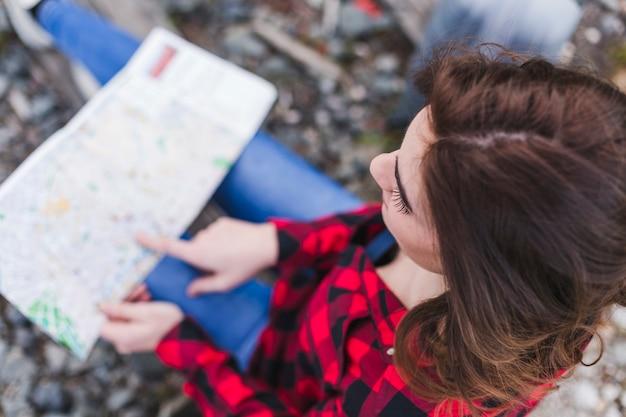 Взгляд сверху молодой красивой женщины используя или смотря карту.